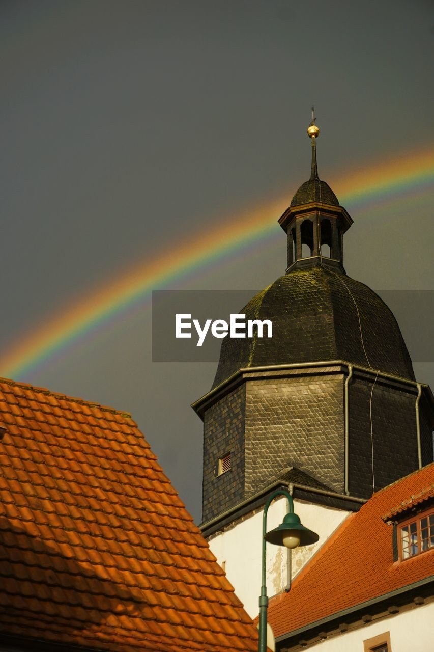 LOW ANGLE VIEW OF BUILDING AGAINST RAINBOW IN SKY