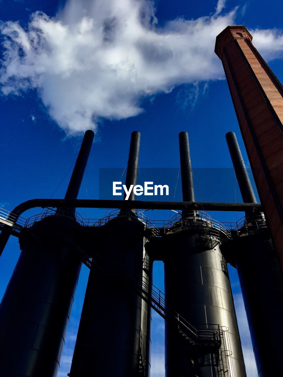 sky, cloud - sky, low angle view, industry, nature, factory, metal, built structure, no people, architecture, day, fuel and power generation, building exterior, blue, outdoors, business, smoke stack, environment, environmental issues, travel, pollution