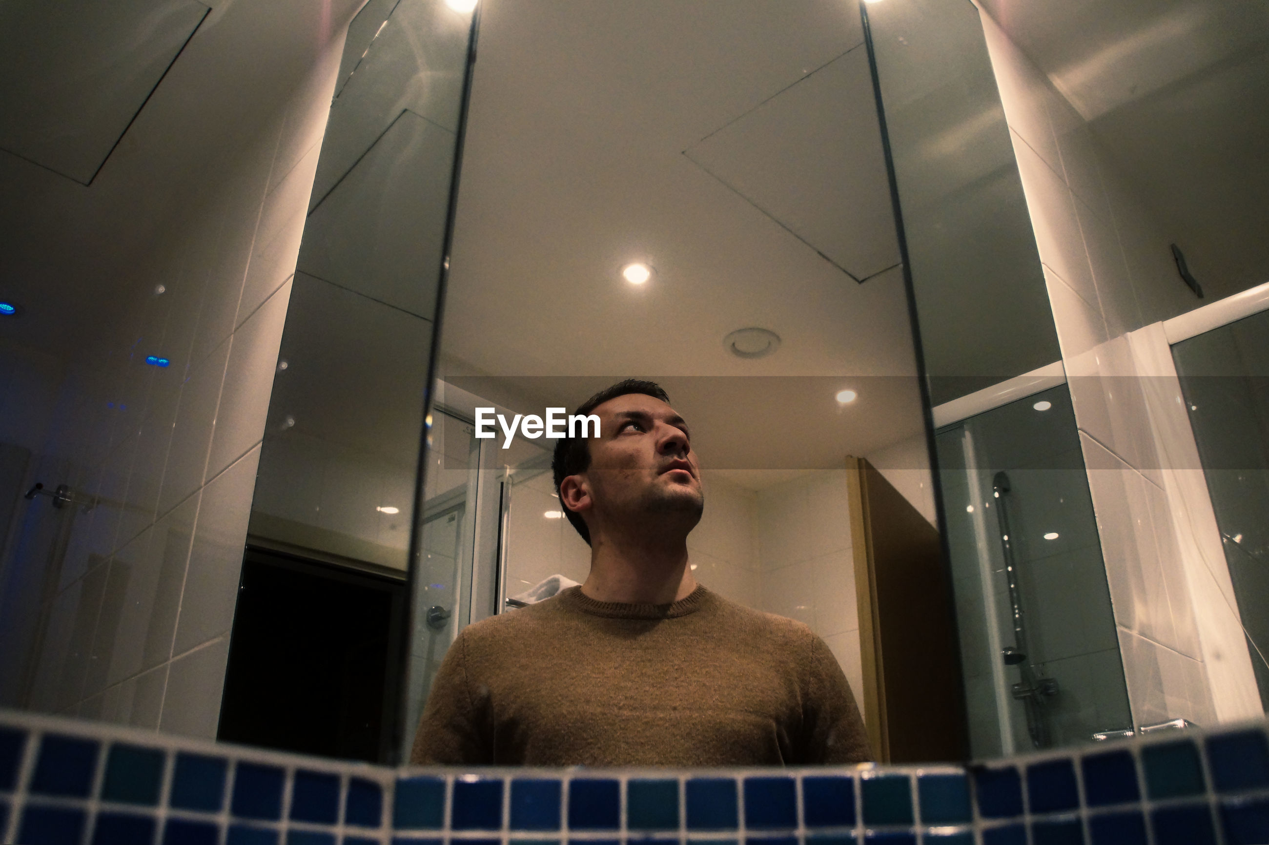 Low angle view of young man looking away reflecting on mirror in bathroom