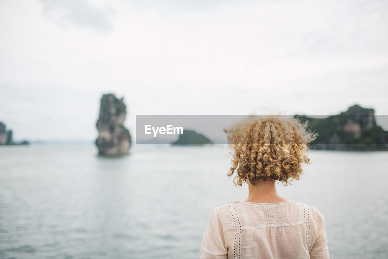 Rear view of woman with curly hair looking at sea against sky