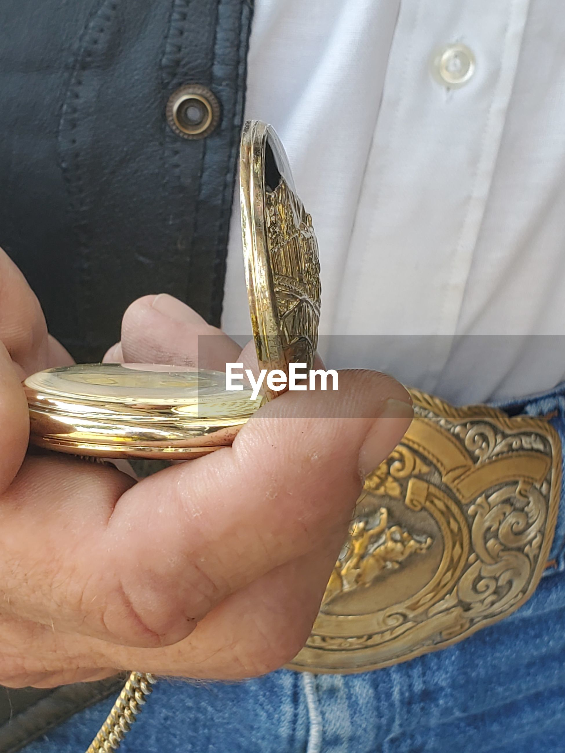 Midsection of person holding gold colored pocket watch
