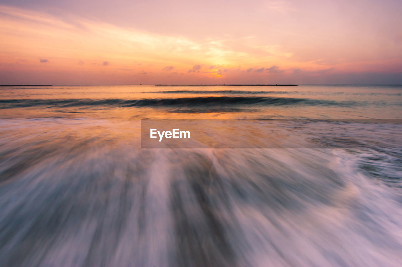 sunset, sea, sky, water, scenics - nature, horizon over water, horizon, beauty in nature, motion, long exposure, tranquility, beach, cloud - sky, tranquil scene, orange color, blurred motion, land, no people, idyllic, outdoors