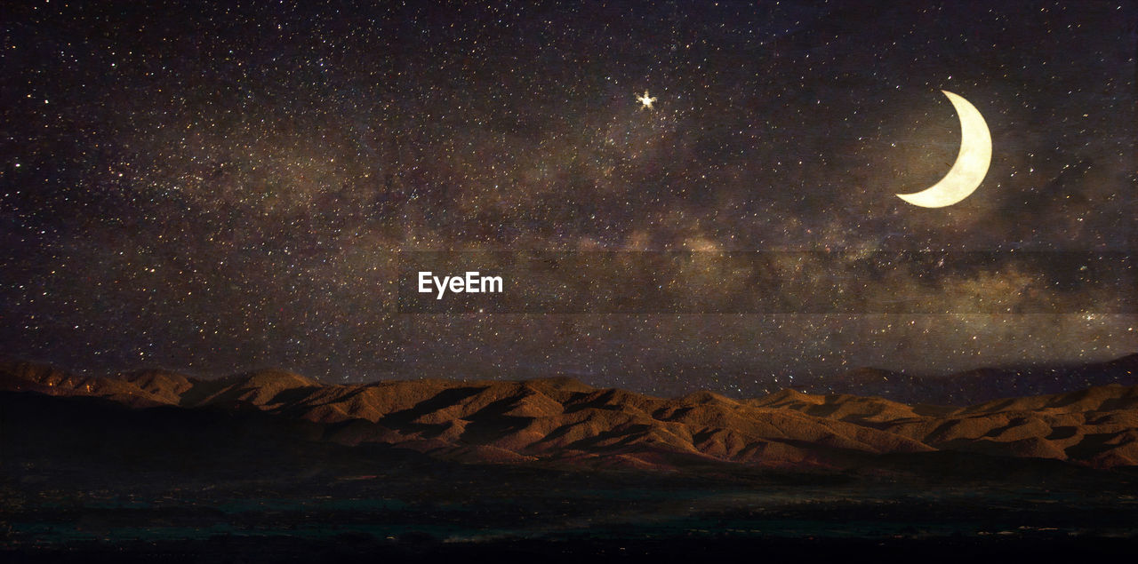Crescent Moon With Constellation Over Mountains In Desert At Night