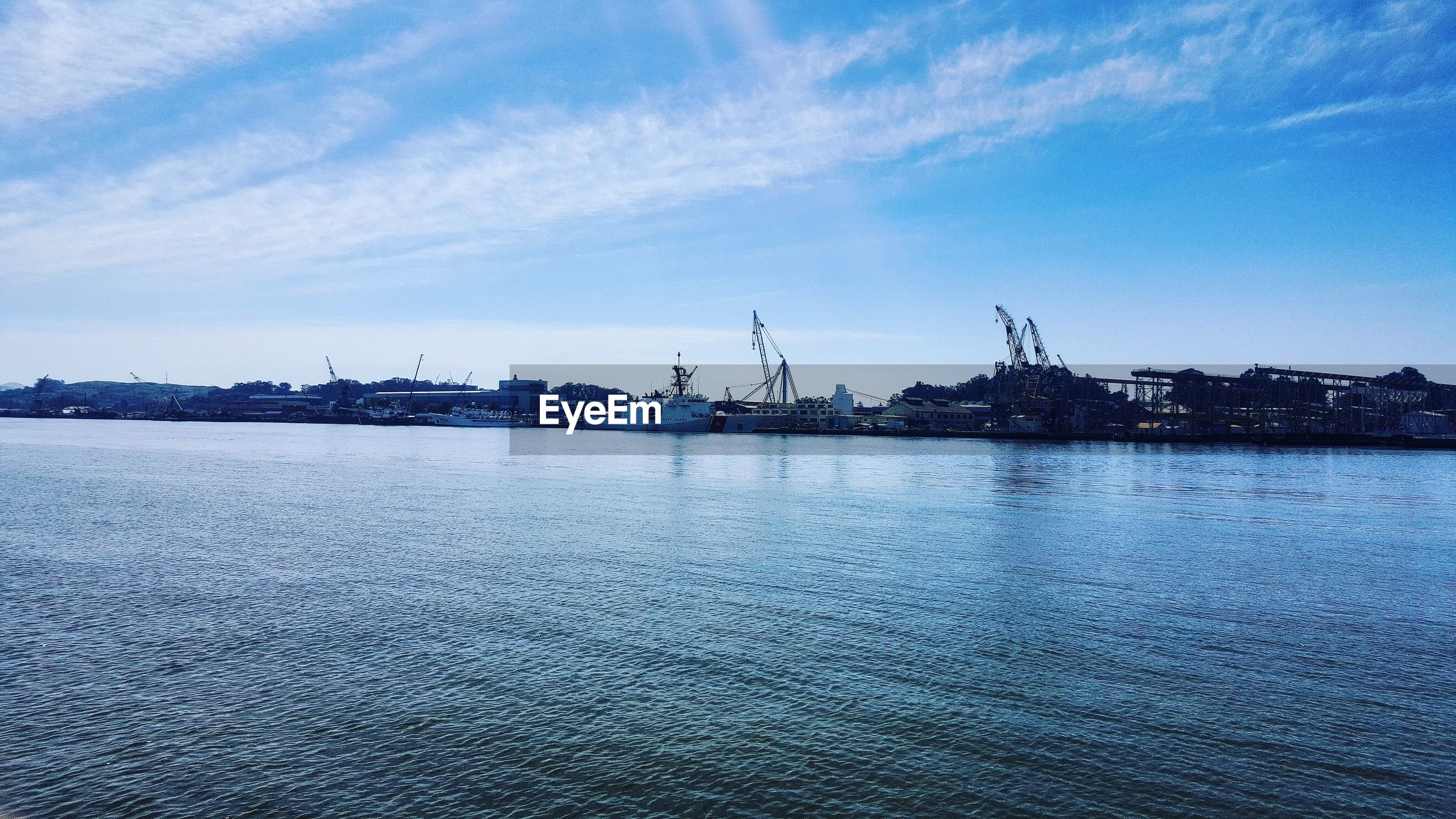 water, waterfront, sky, blue, sea, nautical vessel, cloud - sky, harbor, built structure, building exterior, transportation, nature, tranquility, cloud, tranquil scene, rippled, architecture, scenics, mode of transport, outdoors