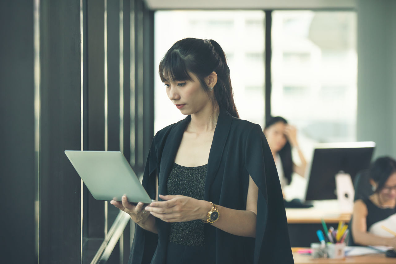Businesswoman using laptop while standing in office