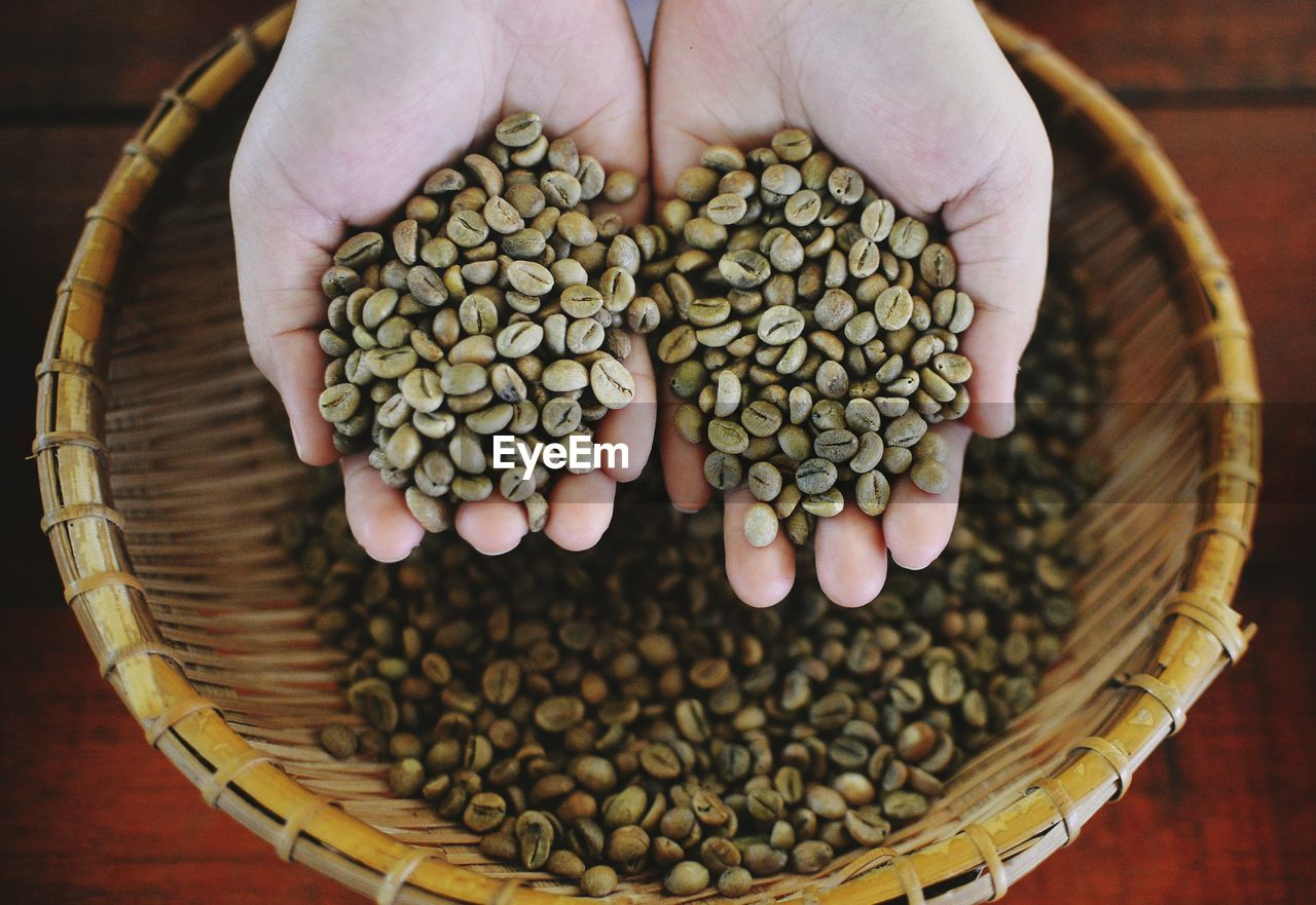 High Angle View Of Hands Holding Raw Coffee Beans Over Basket
