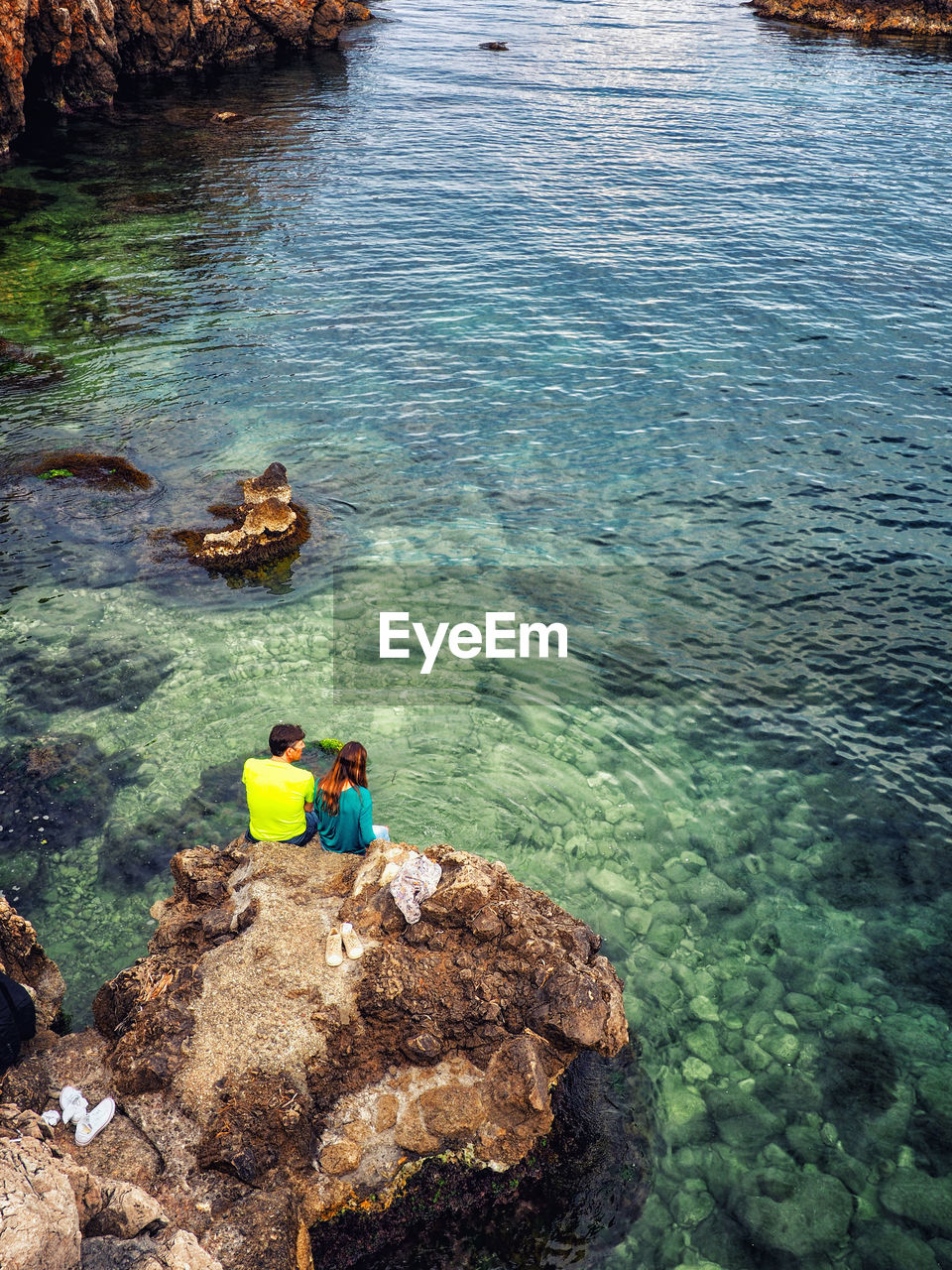 water, rock, solid, rock - object, high angle view, real people, men, sea, day, togetherness, nature, people, beauty in nature, women, sitting, leisure activity, lifestyles, outdoors, turquoise colored