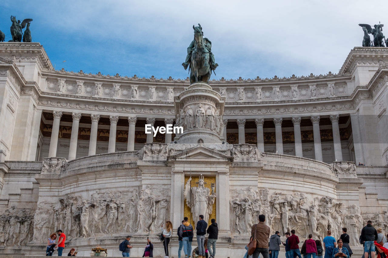 architecture, built structure, group of people, sculpture, tourism, real people, travel destinations, art and craft, human representation, building exterior, travel, large group of people, representation, statue, women, crowd, sky, history, the past, men, outdoors, architectural column