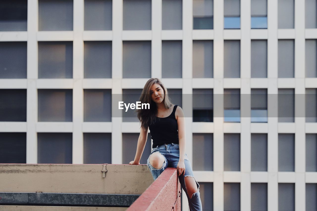 Portrait of young woman wearing torn jeans sitting on railing against modern building