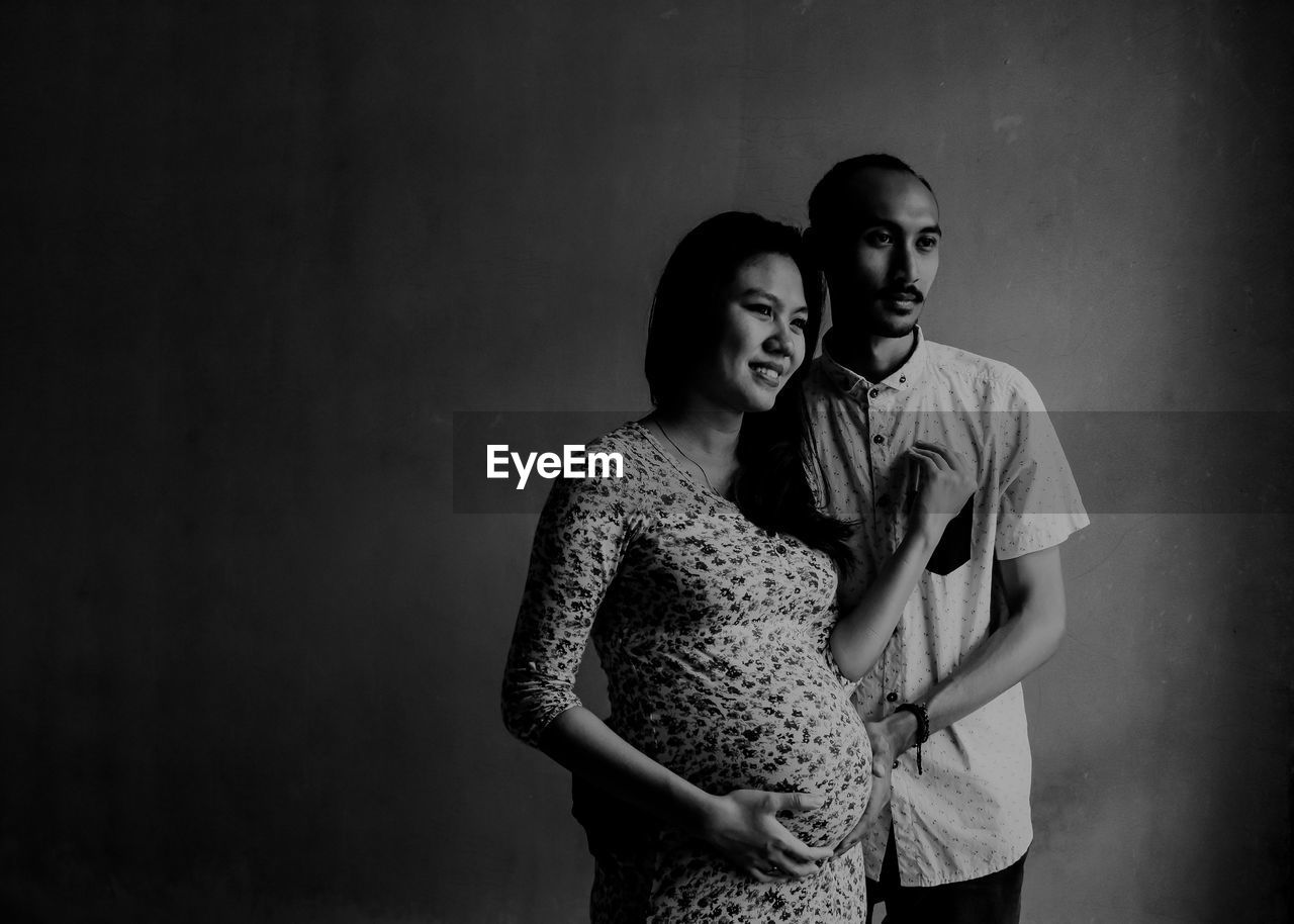 Man With Pregnant Wife Standing Against Wall