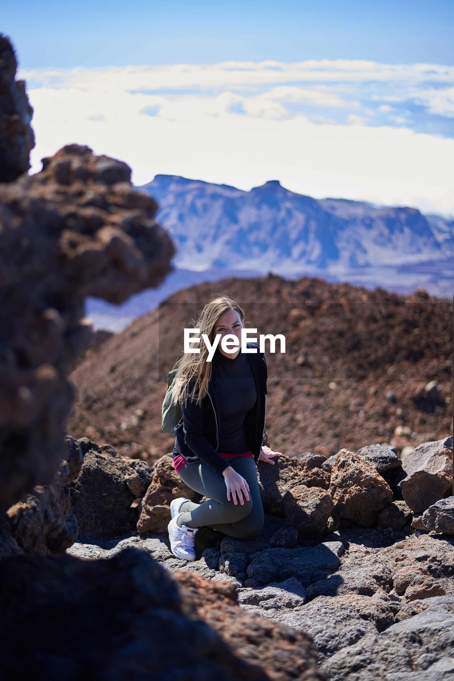 Portrait of young woman sitting on rock against mountains and sky