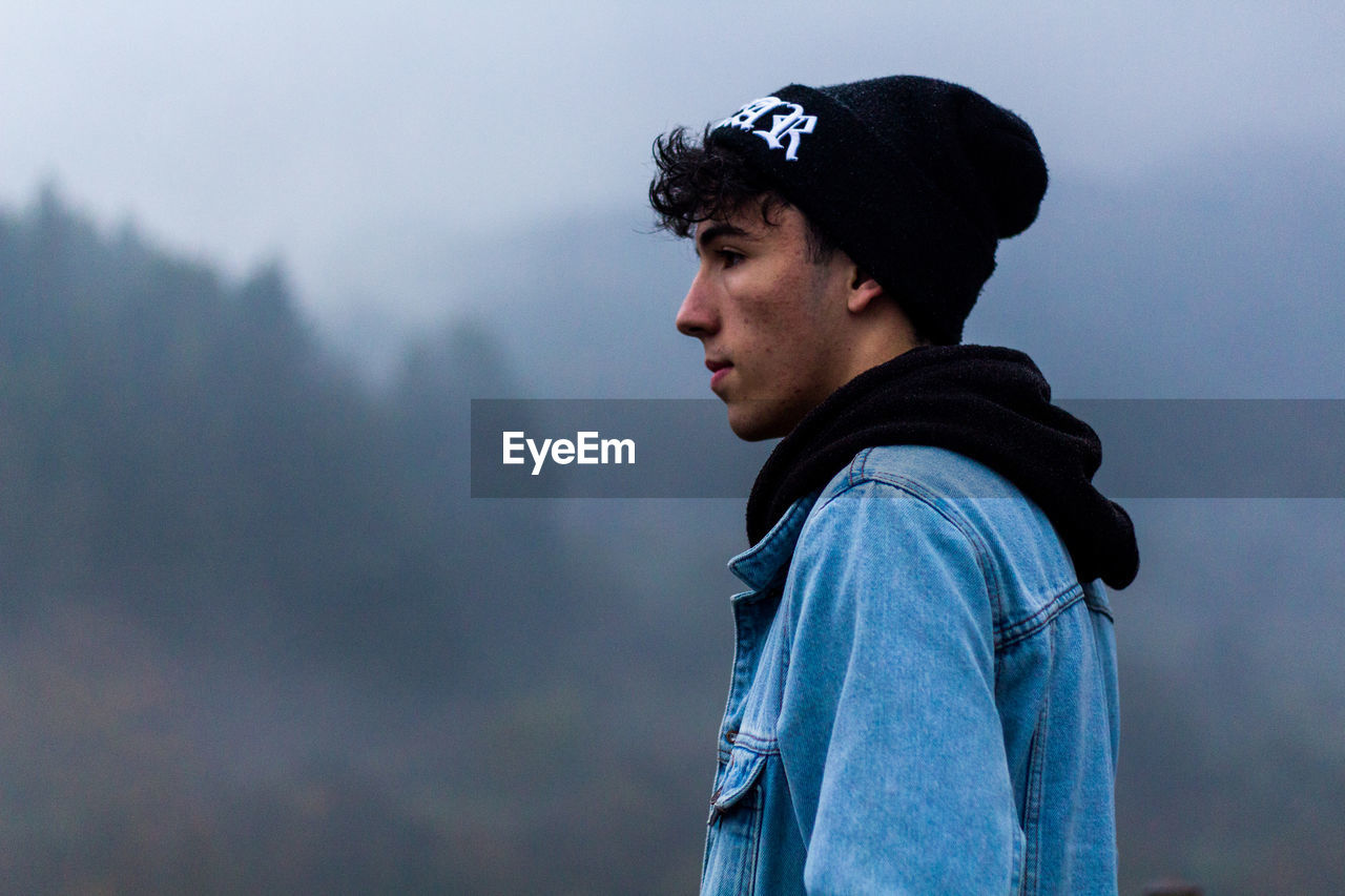 Side View Of Handsome Young Man Wearing Knit Hat During Foggy Weather
