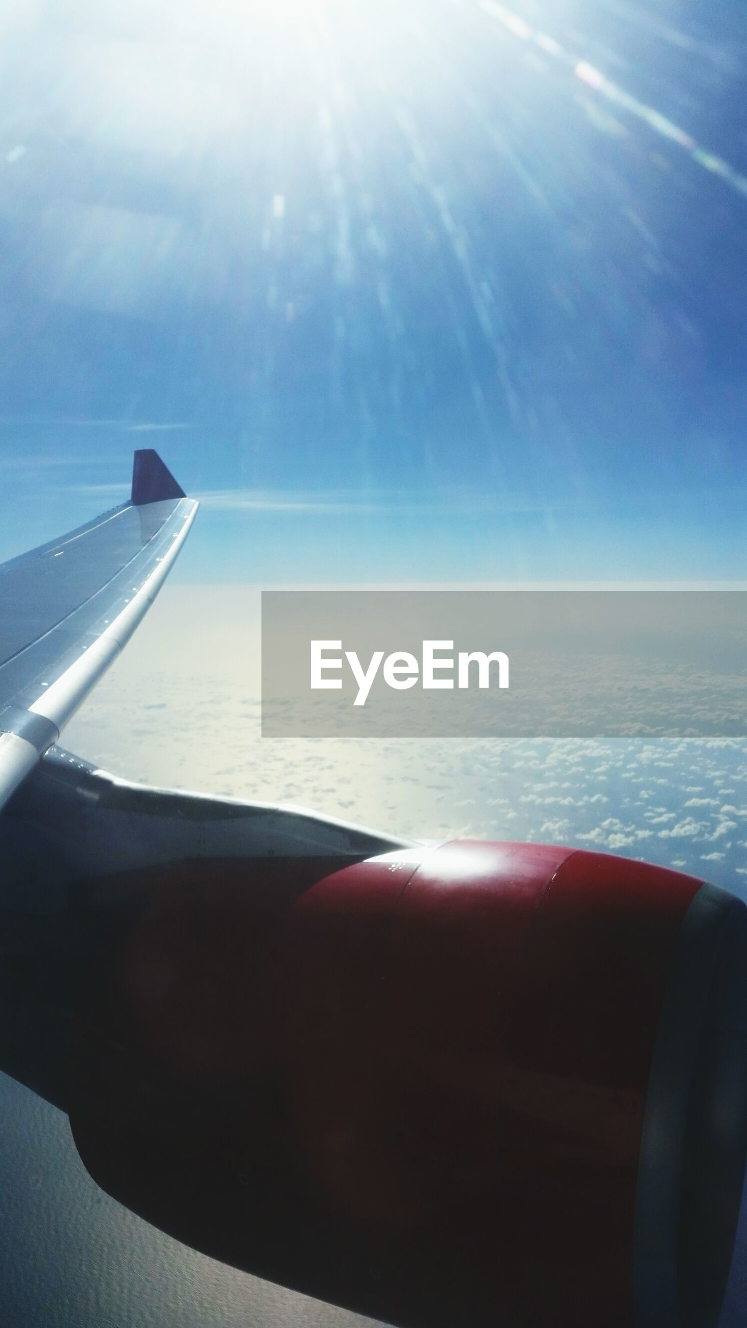 CROPPED IMAGE OF AIRPLANE WING OVER SEA