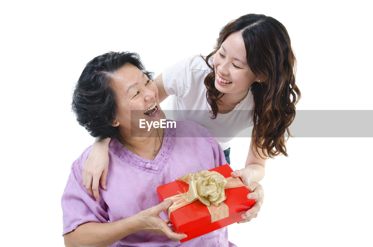 Daughter giving gift to mother against white background
