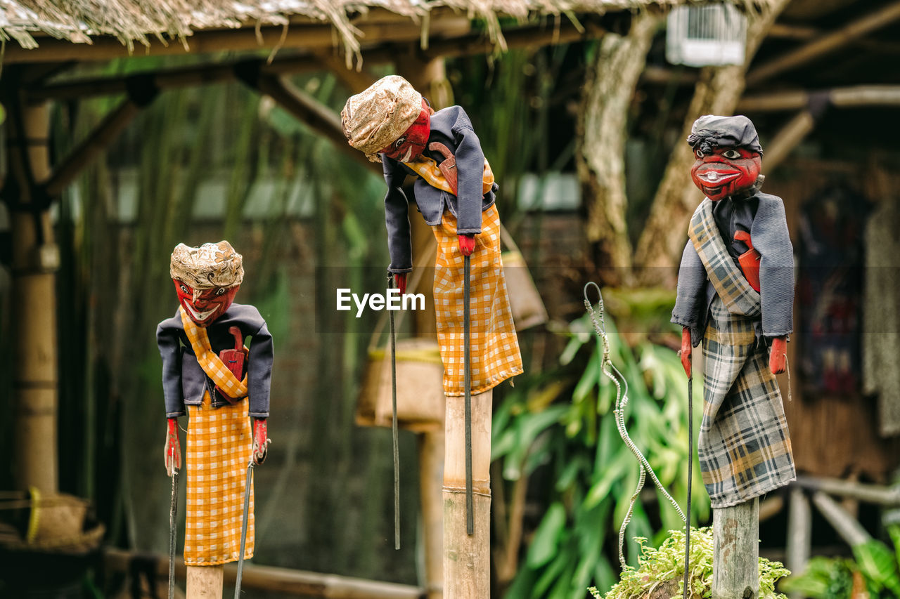 Toys hanging on wooden poles against house