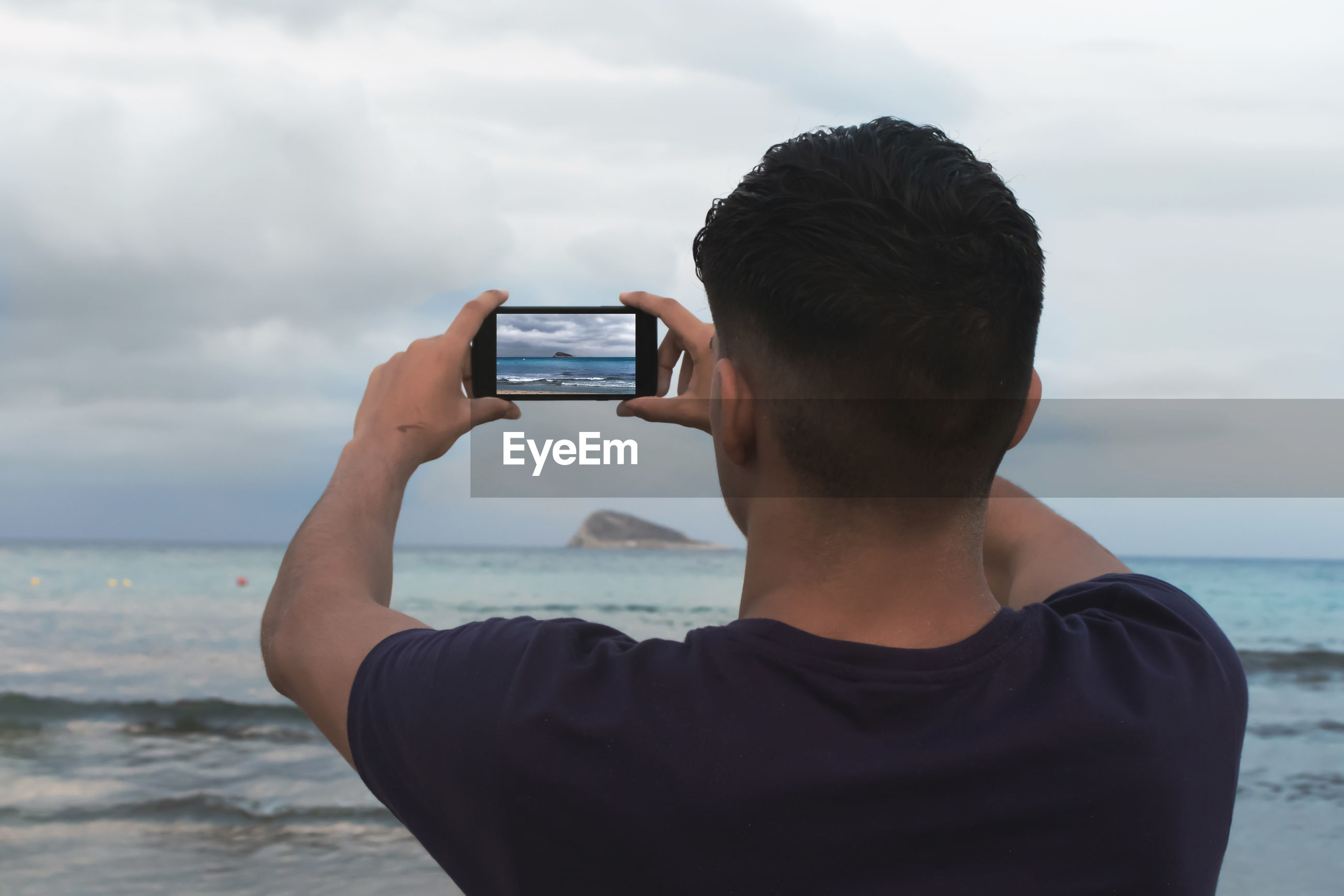 Rear view of teenage boy photographing sea with mobile phone against sky