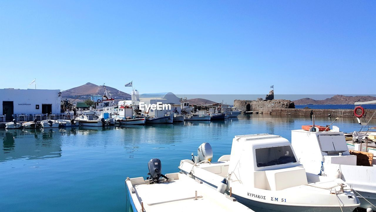 BOATS MOORED ON SEA BY BUILDINGS AGAINST CLEAR SKY