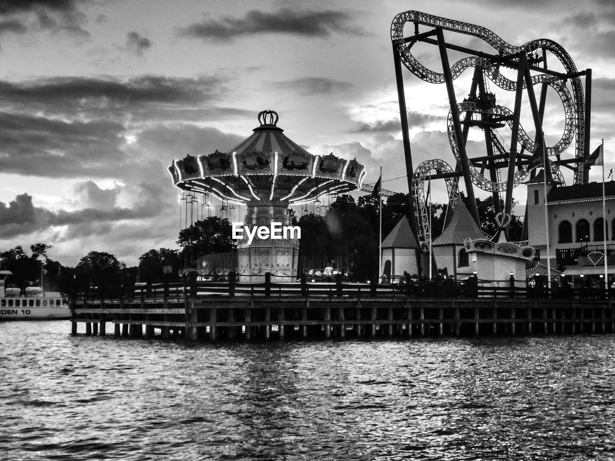 architecture, built structure, sky, water, building exterior, waterfront, cloud - sky, river, cloud, cloudy, rippled, tree, outdoors, low angle view, no people, reflection, day, ferris wheel, connection, travel destinations