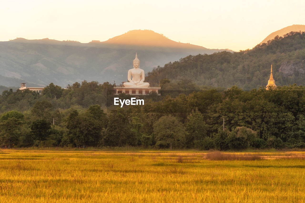 mountain, religion, tree, spirituality, no people, nature, scenics, architecture, landscape, sunset, mountain range, tranquil scene, place of worship, beauty in nature, travel destinations, outdoors, built structure, tranquility, day, building exterior, clear sky, sky