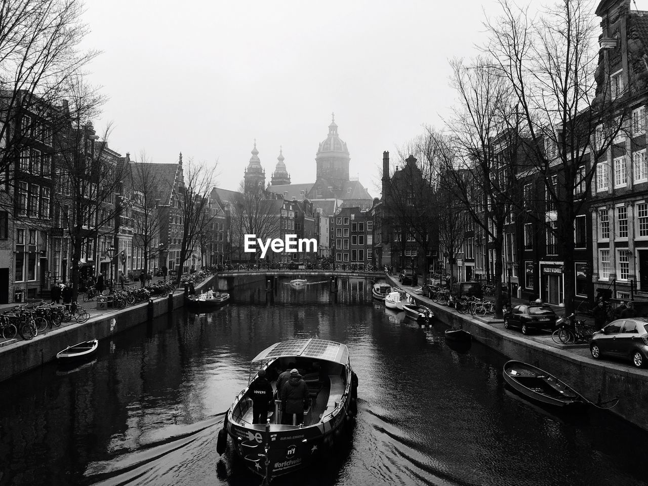 Boat moving in canal amidst buildings against clear sky