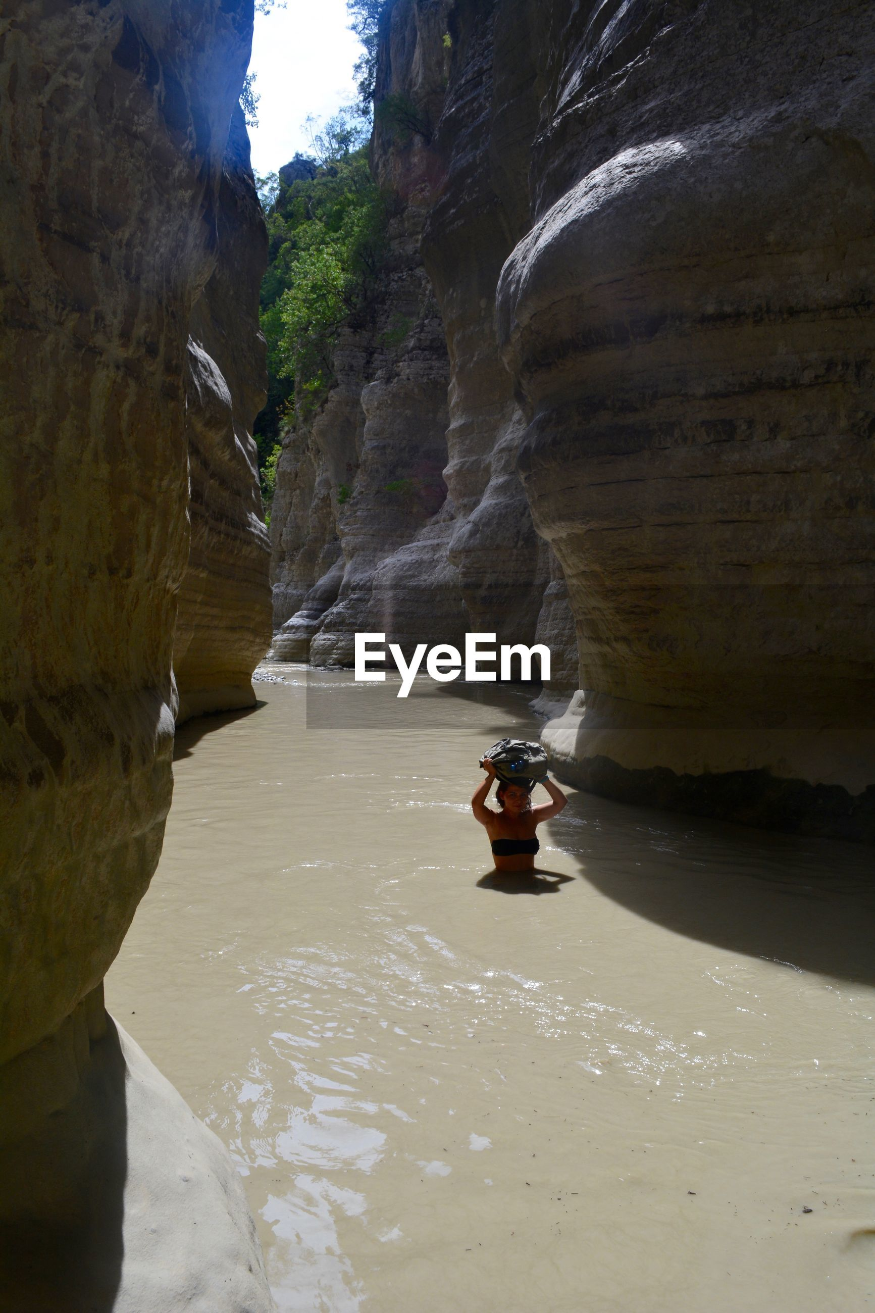 High angle view of woman in river amidst rock formations
