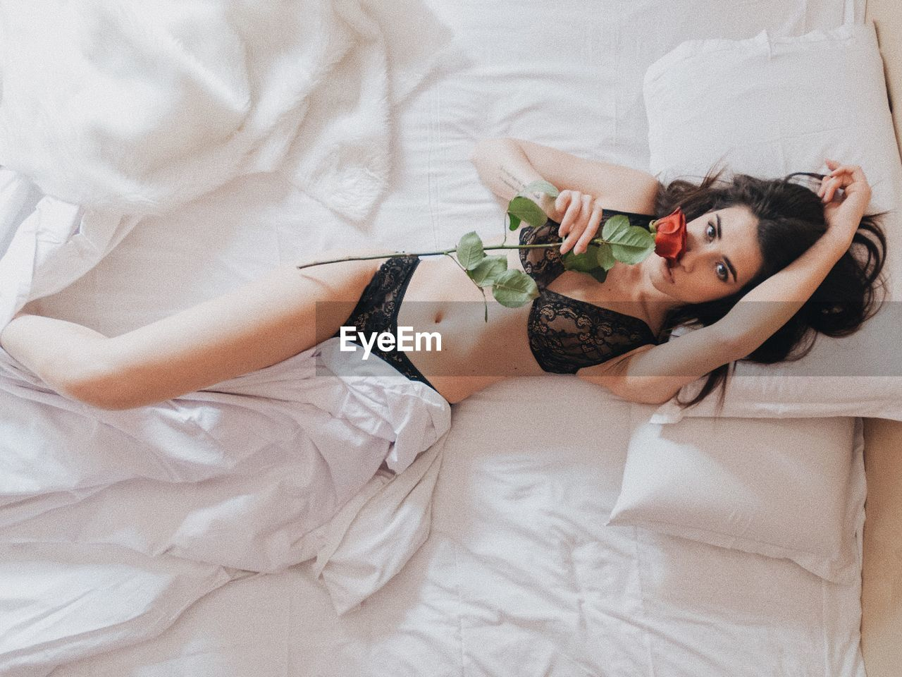 Directly Above View Of Woman Lying With Rose On Bed At Home
