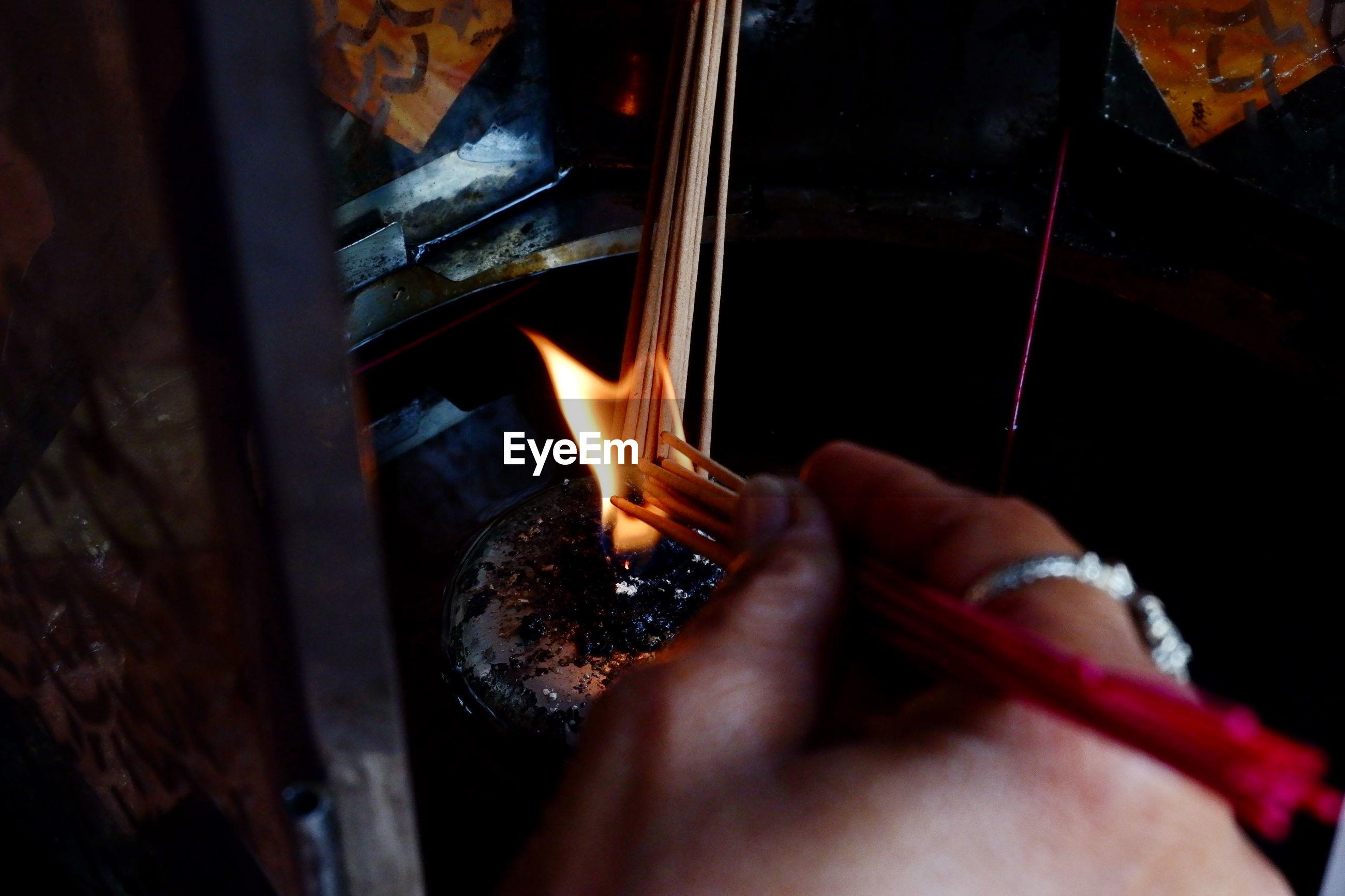 Close-up of hand burning incense