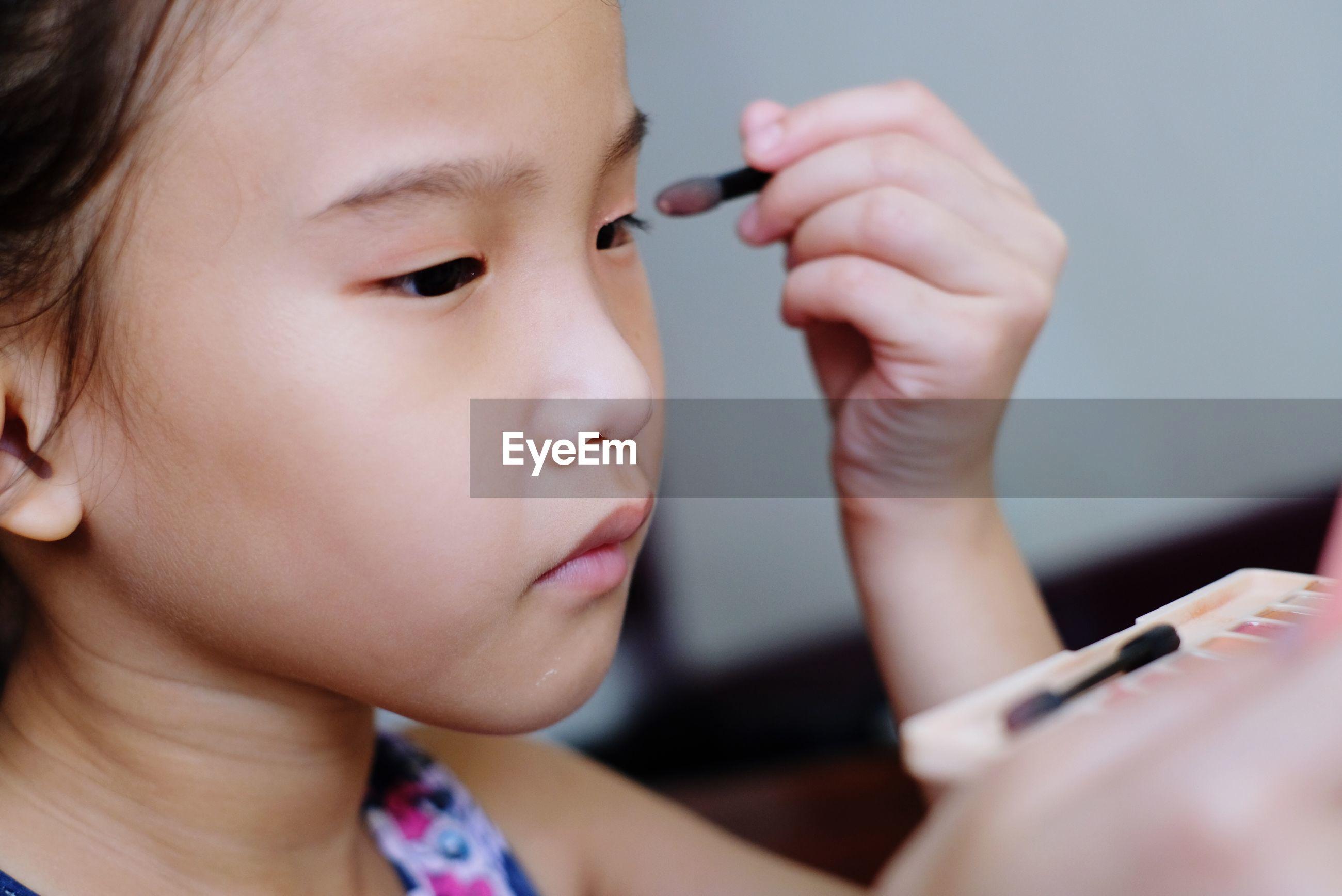 Close-up of cute girl applying make-up