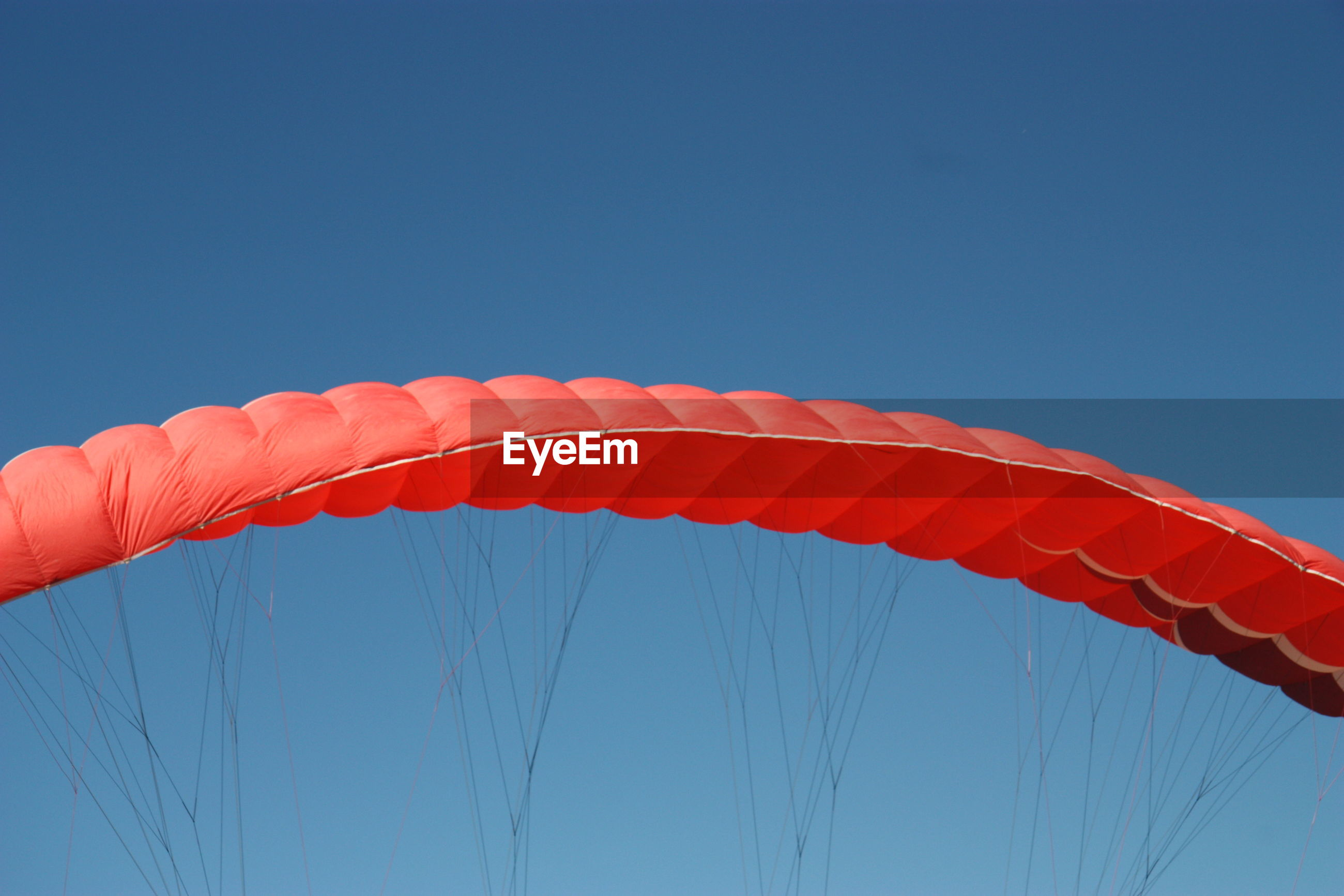 Low angle view of parachute flying against blue sky