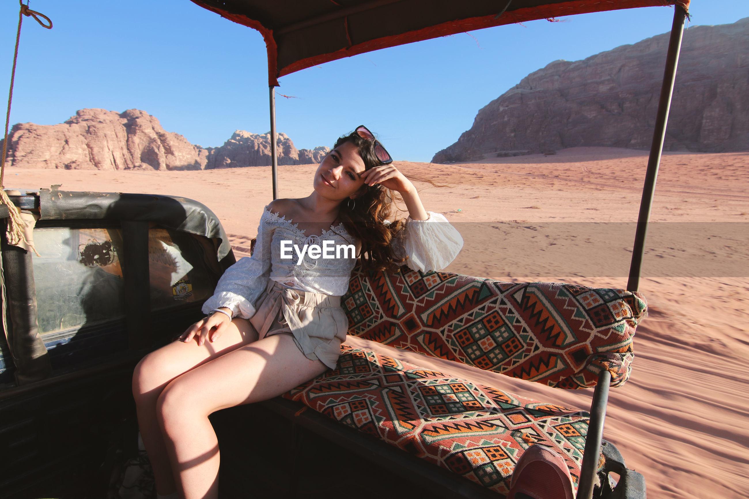 Woman sitting on car riding through desert against mountains