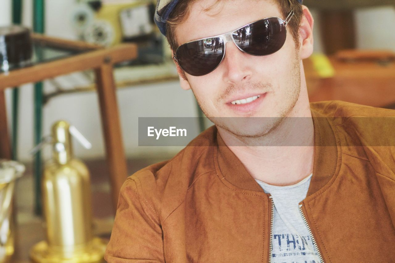 Close-up of young man wearing sunglasses and brown jacket