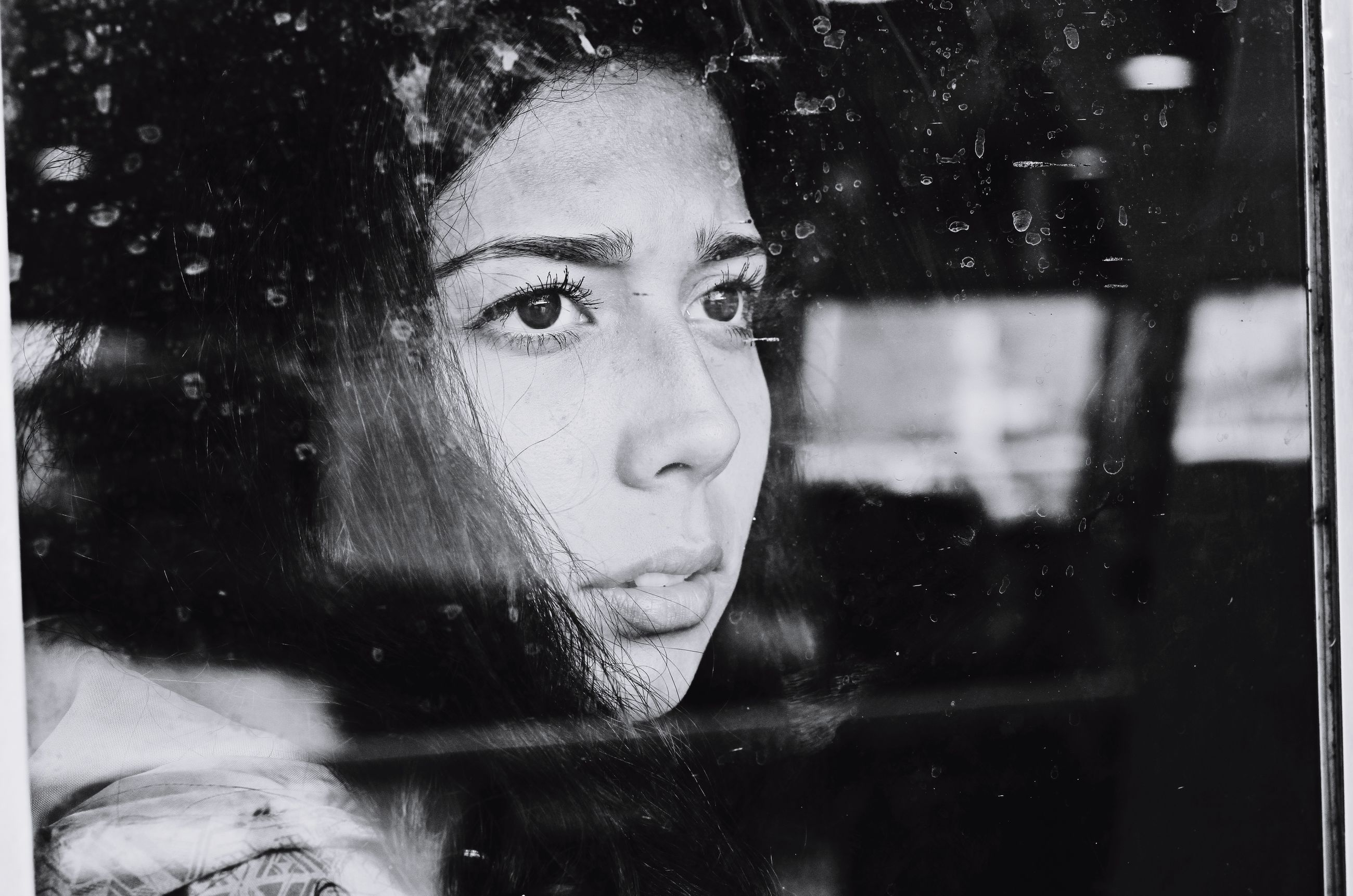 Close-up of young woman looking through window