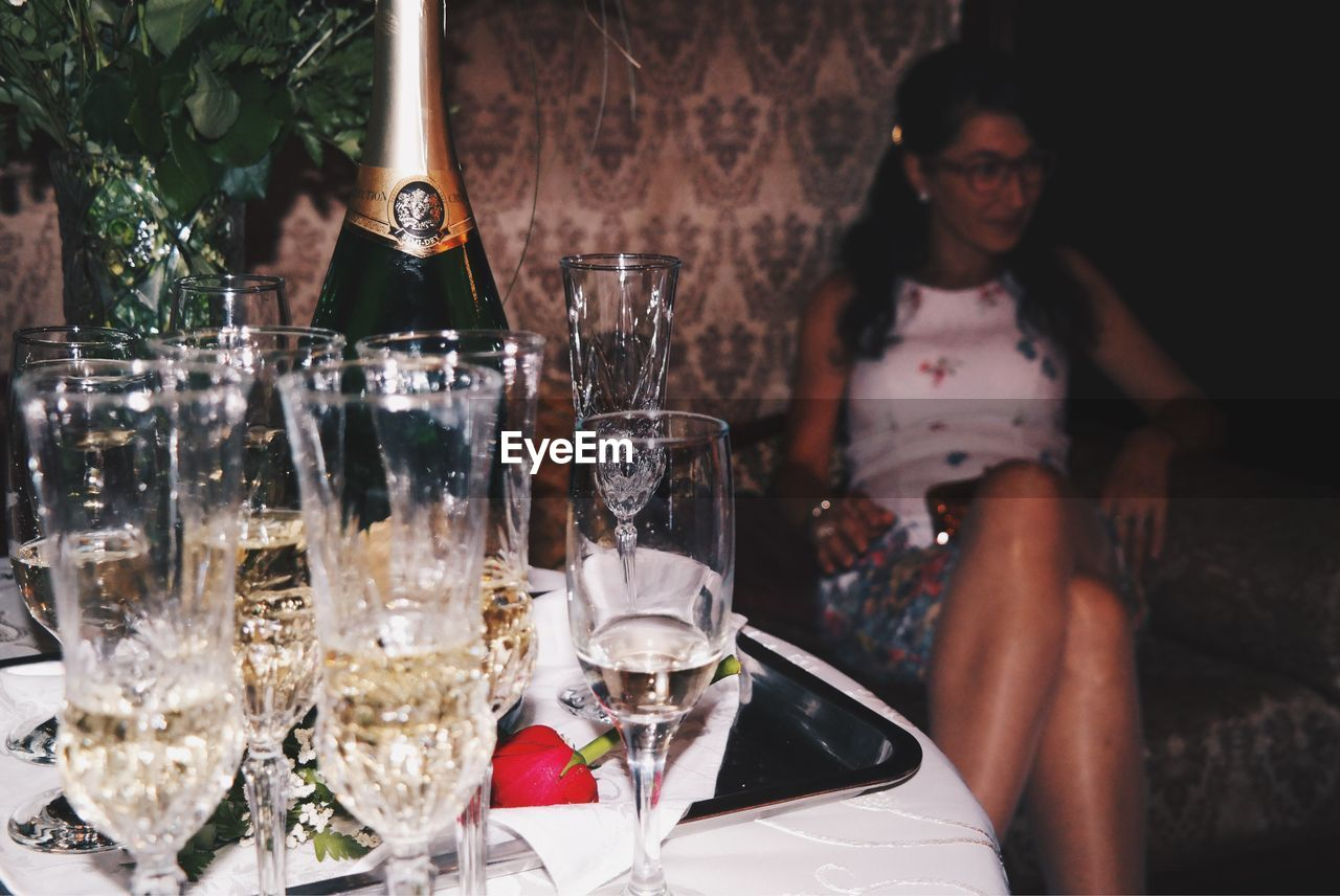 Champagne On Table With Woman Sitting In Background At Restaurant