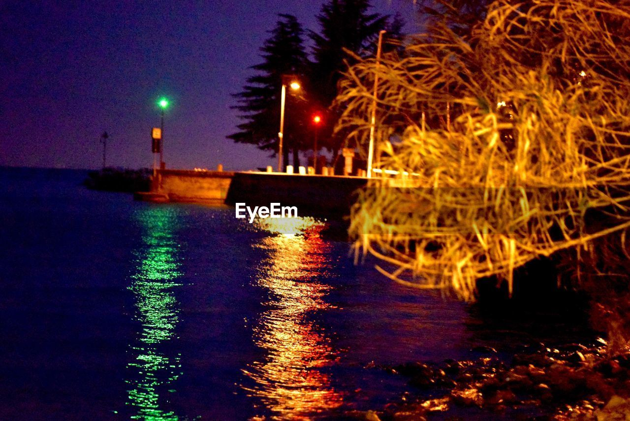 night, illuminated, water, celebration, tree, lighting equipment, nature, reflection, architecture, no people, street, motion, street light, city, light, outdoors, built structure, building exterior, waterfront