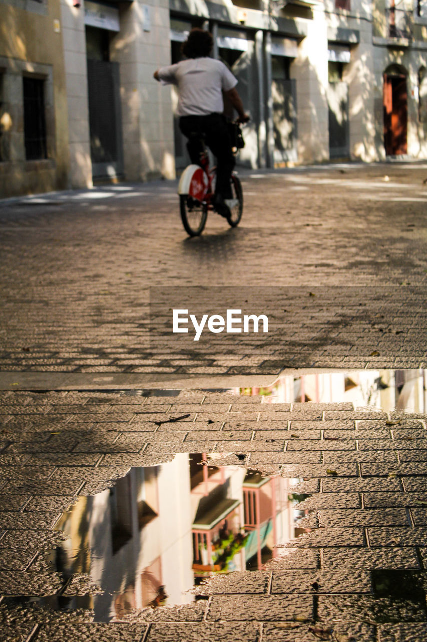 bicycle, transportation, architecture, built structure, real people, mode of transportation, one person, land vehicle, building exterior, lifestyles, men, city, ride, street, riding, building, day, leisure activity, motion, outdoors, architectural column