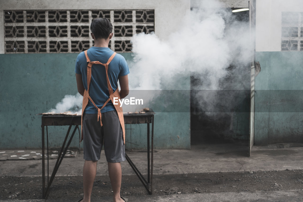 smoke - physical structure, one person, rear view, casual clothing, men, real people, architecture, built structure, males, lifestyles, building exterior, day, leisure activity, holding, full length, boys, seat, standing, child, outdoors, shorts, uniform