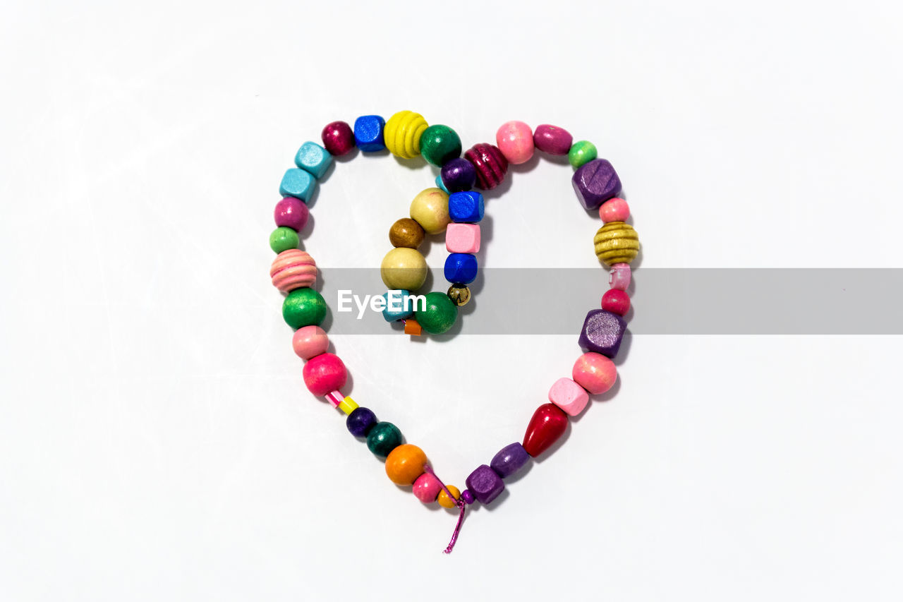 studio shot, white background, still life, multi colored, indoors, copy space, high angle view, large group of objects, no people, close-up, art and craft, choice, bead, directly above, shape, variation, jewelry, circle, geometric shape, creativity