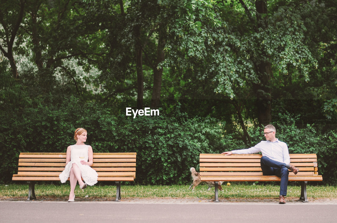 bench, two people, sitting, full length, togetherness, park - man made space, young adult, relaxation, tree, young women, smiling, casual clothing, day, leisure activity, front view, love, outdoors, looking at camera, couple - relationship, young couple, legs crossed at knee, young men, medium-length hair, growth, happiness, arms crossed, nature, women, adult, bonding, adults only, cheerful, portrait, people, sky