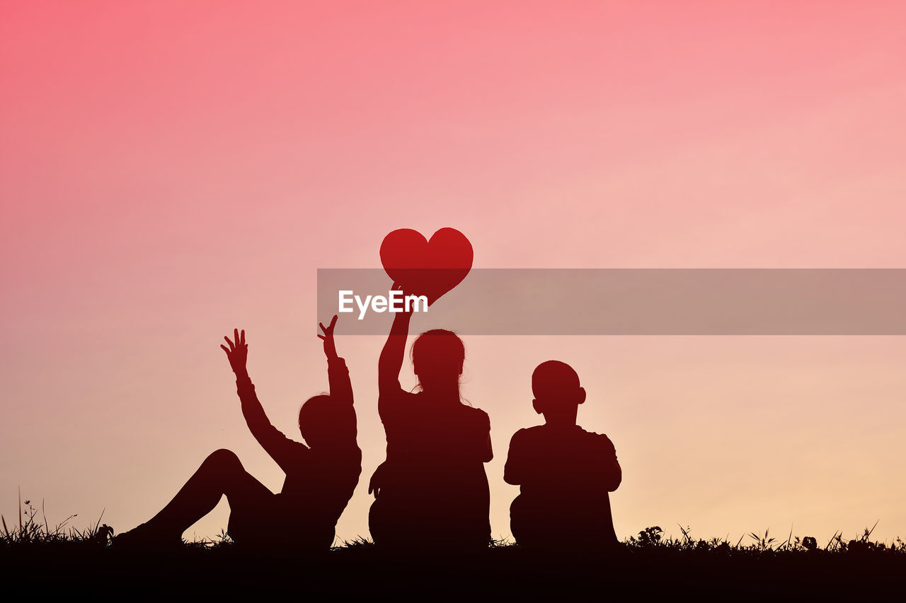 Silhouette Mother Holding Heart Shape With Children On Field Against Sky During Sunset