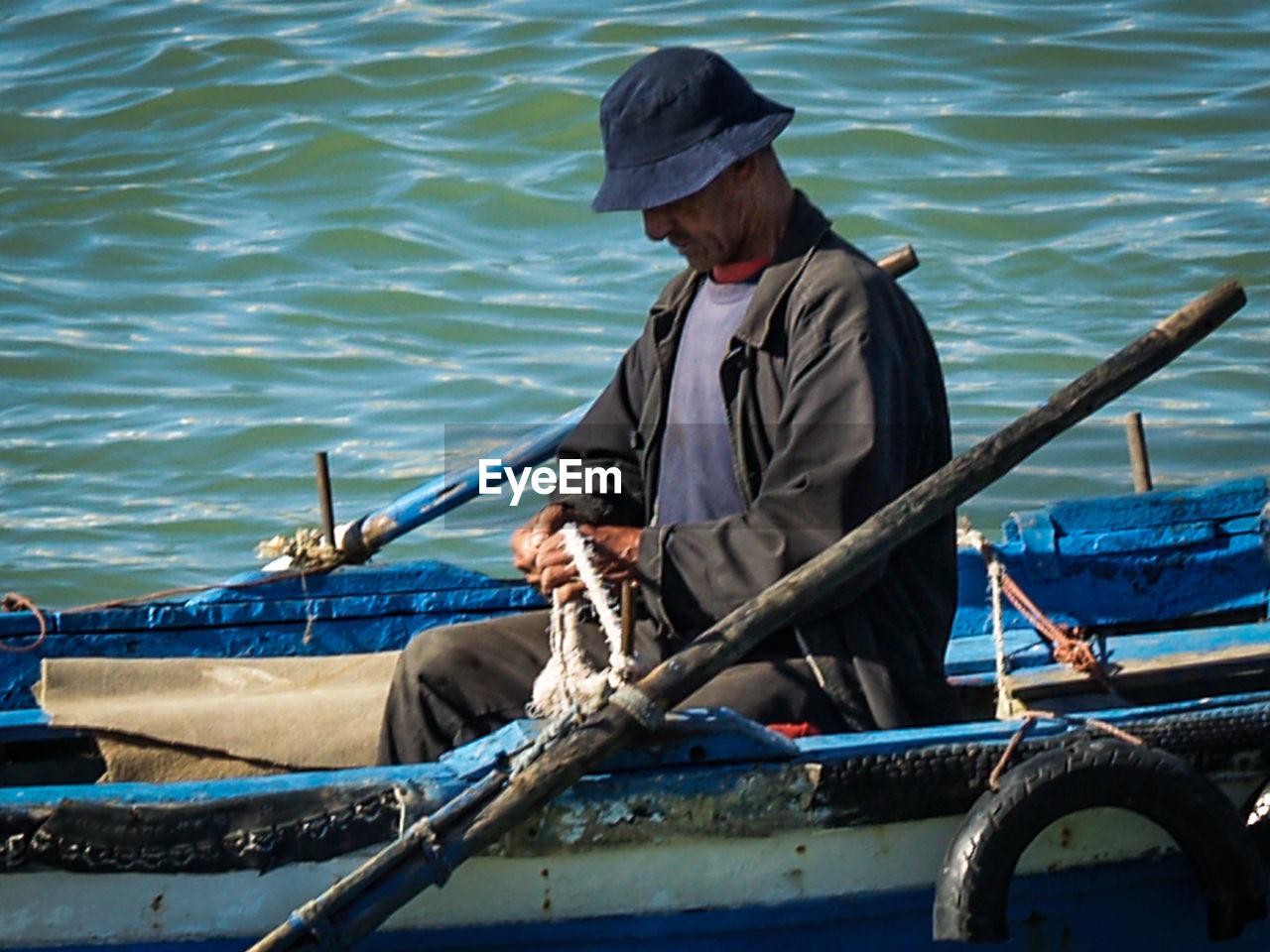 MAN FISHING BOAT SAILING IN SEA