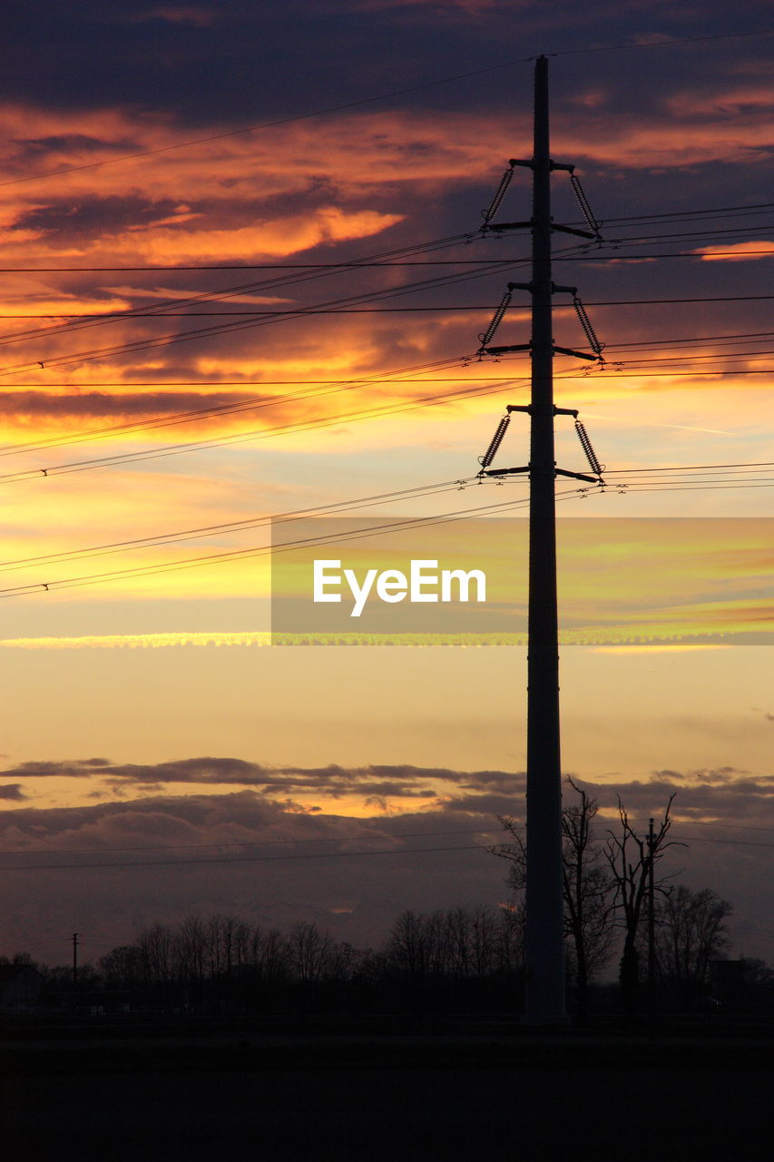 Power lines on field against sky during sunset