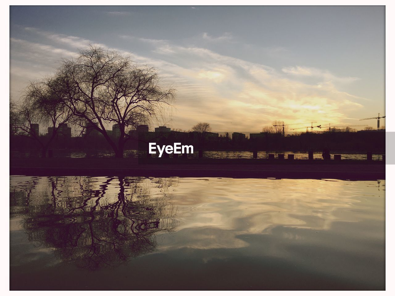 reflection, sky, water, tree, cloud - sky, building exterior, outdoors, architecture, built structure, river, bare tree, nature, no people, city, beauty in nature, tranquility, travel destinations, sunset, scenics, day