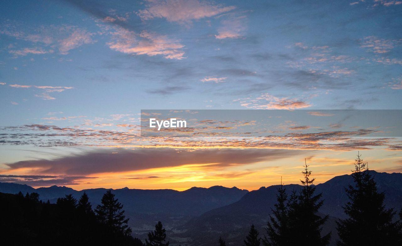 sky, cloud - sky, beauty in nature, sunset, scenics - nature, tranquility, tranquil scene, mountain, tree, silhouette, orange color, nature, plant, idyllic, non-urban scene, no people, mountain range, environment, outdoors, landscape, coniferous tree, mountain peak