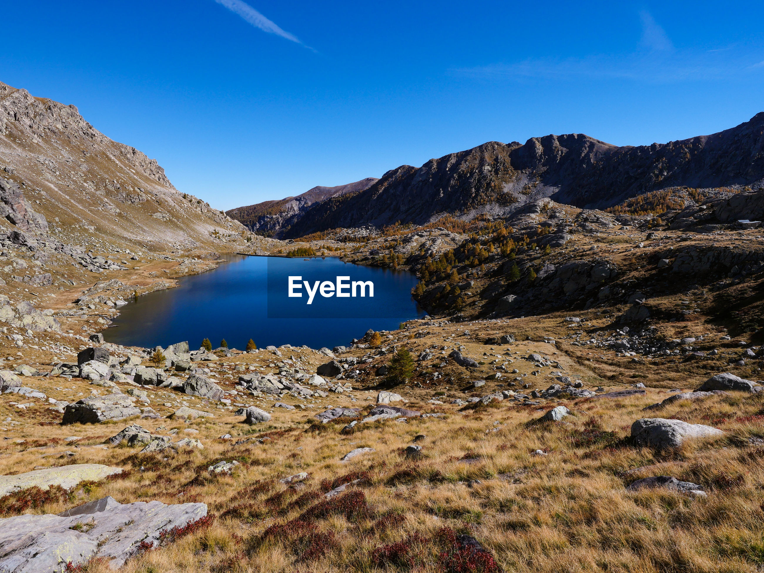 SCENIC VIEW OF LAKE AND MOUNTAIN AGAINST BLUE SKY