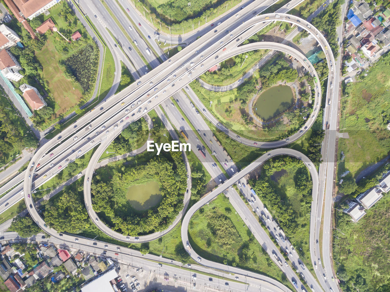 road, aerial view, transportation, high angle view, highway, plant, city, street, mode of transportation, day, no people, nature, multiple lane highway, elevated road, overpass, land vehicle, landscape, green color, tree, environment, outdoors