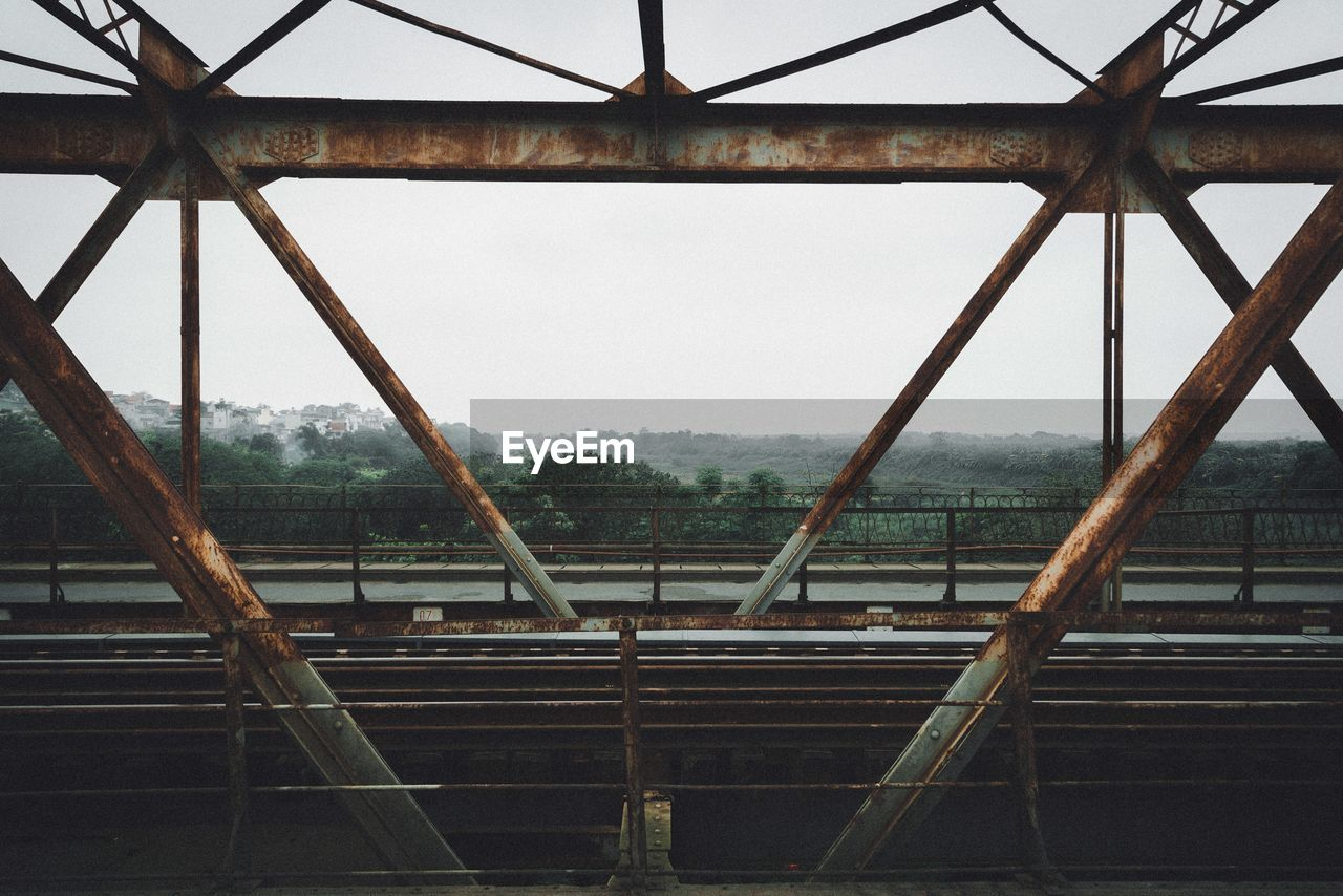 metal, no people, architecture, built structure, rusty, sky, day, nature, abandoned, clear sky, outdoors, tree, decline, old, deterioration, low angle view, water, obsolete, damaged, roof beam