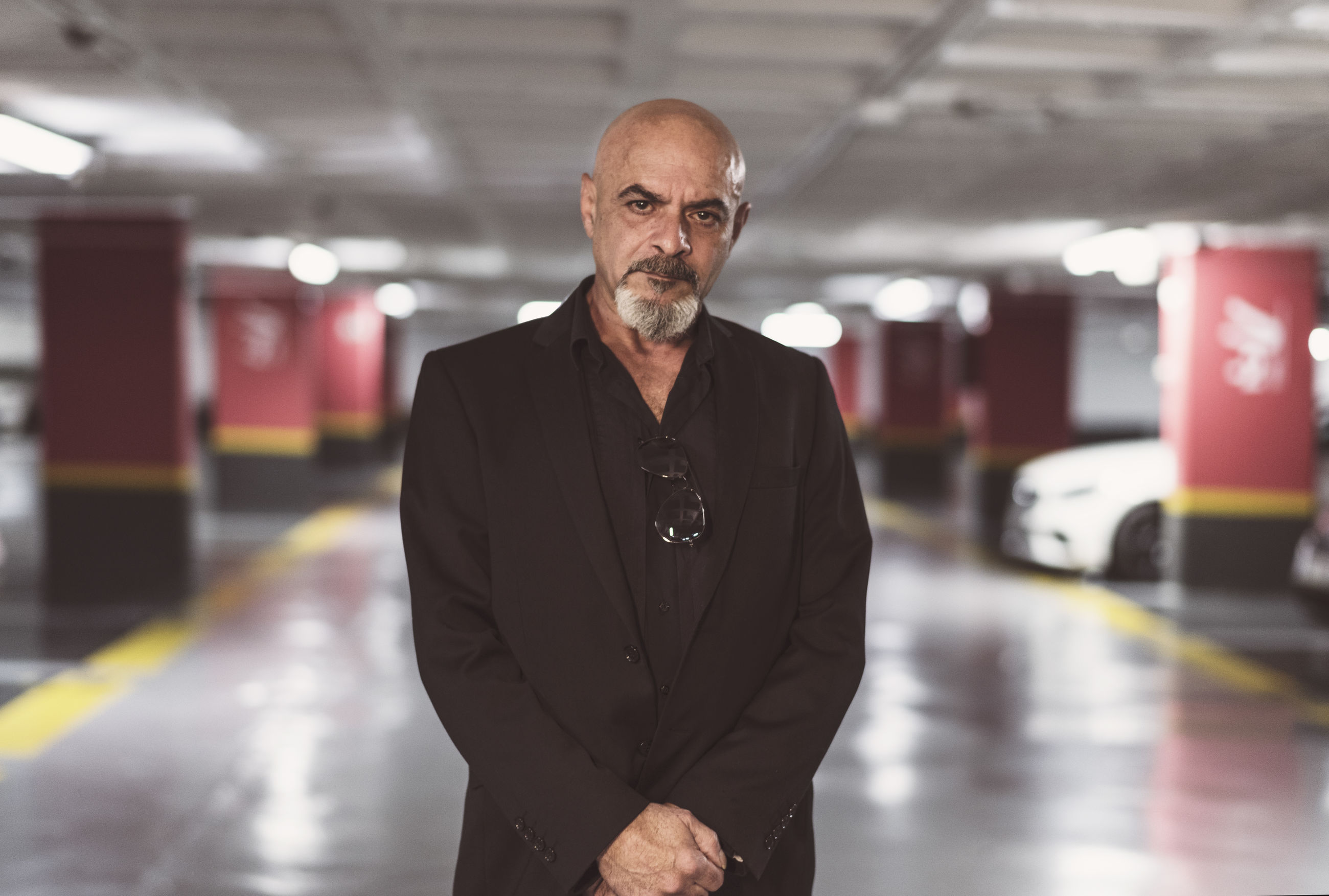Portrait of bald businessman standing in garage