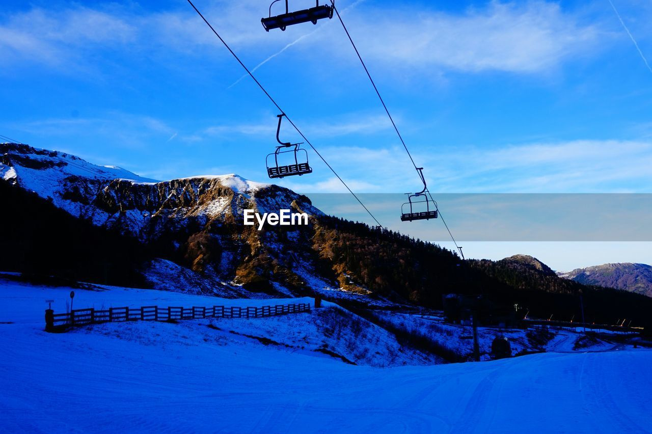 Low angle view of overhead cable cars over snow covered field against sky