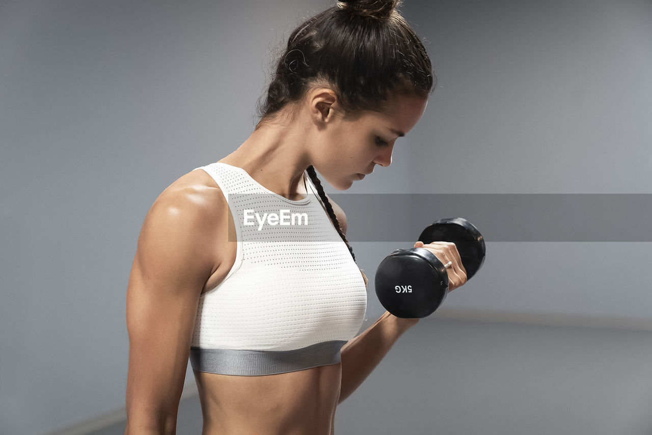 one person, lifestyles, strength, healthy lifestyle, indoors, standing, sport, holding, exercising, front view, dumbbell, weights, adult, sports training, gray, muscular build, weight, gray background, women, weight training, hairstyle