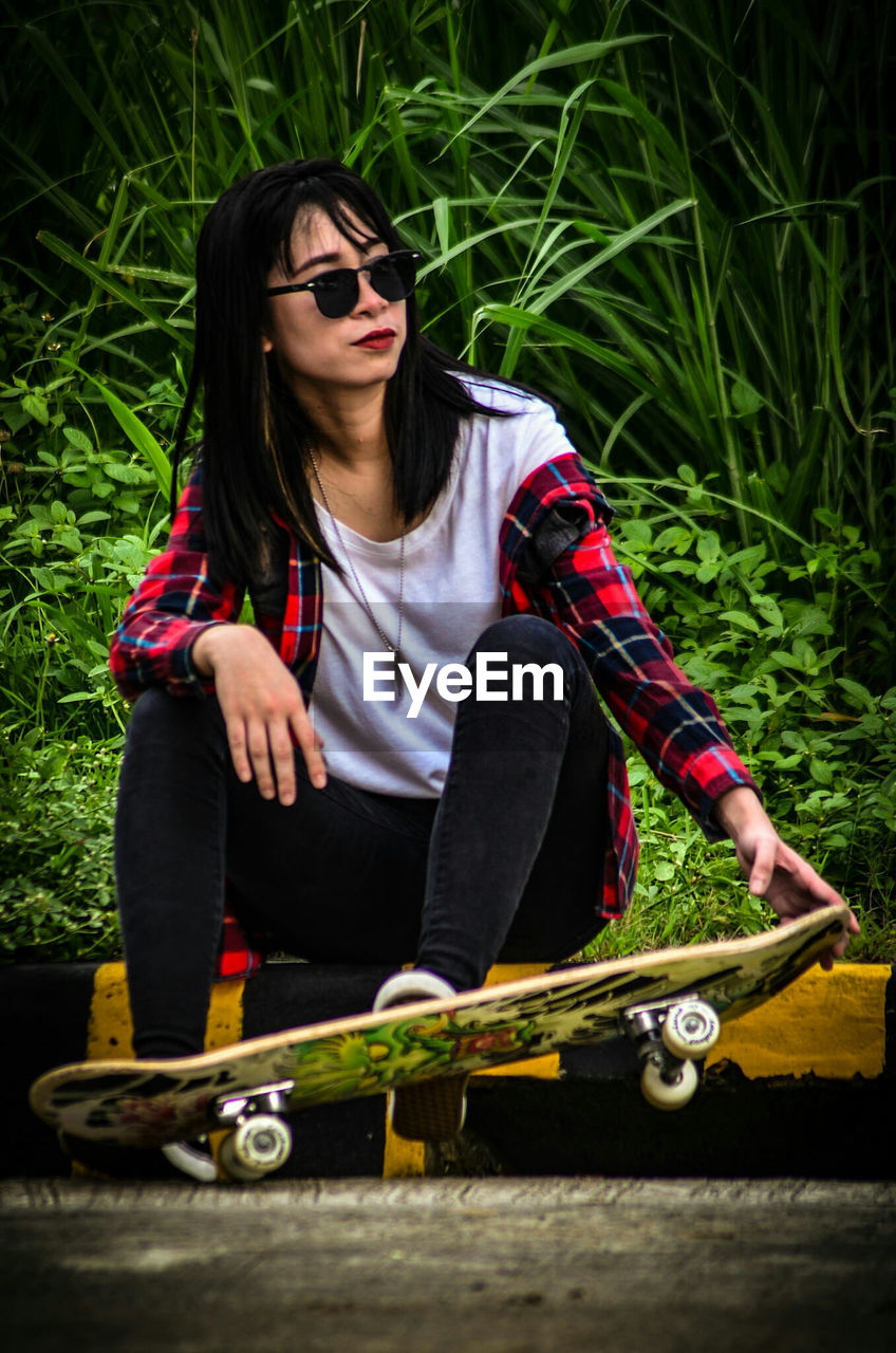 Woman In Sunglasses With Skateboard At Park